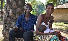 Photo of a man and woman posing outside with their infant child
