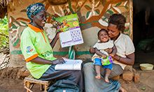 Photo of community health worker showing a mother (holding her young child) the MNP calendar