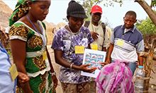 Photo of a group of women and men gathering to look at a flyer on handwashing.