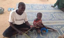 Man and child sit on a mat in Niger