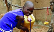 A young girl washes her hands at a tippy tap.