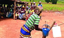 Photo of a woman demonstrating hwo to properly use a tippy tap. Caption: Tippy tap demonstrations in Dinyogu Community and Primary School - in Gushiegu District.
