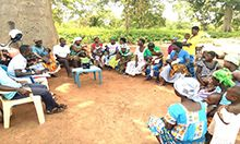 Photo of about a dozen women with their children and several facilitators sitting outside in chairs for a mother-to-mother support group meeting in Ghana