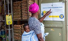 "Photo of a mother, carrying her child on her back, reading a poster inside a store. Caption: ""A mother looks at 'Benefits of fortified foods' poster in Kampala."""
