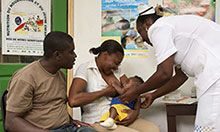 Health worker shows a mother proper breastfeeding techiques while the father looks on