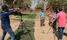 A couple talks to a visitor about growing Indian spinach. The couple explains that their Indian spinach sells quickly in the market. Consumers know how the spinach is grown and that the plant is nutritious. Photo credit: Sarah Hogan, 2017