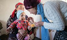 Photo of an older woman holding holding a baby to be spoon-fed by a younger woman.