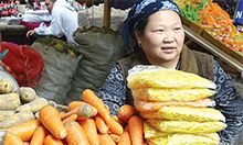 Photo of a woman selling produce at a market