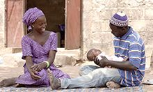Photo of a man and woman sitting on a mat outdoors, with the man holding their infant child.