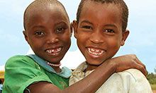 Two children smile at the camera.