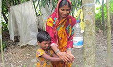 Woman and child washing hands using a Tippy Tap.