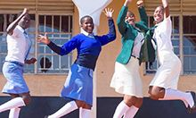 Cover photo: four teenage girls in their school uniforms, dancing and jumping as they pose for the camera.
