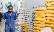 Maize mill employee Haruna Ssemakula carries a sack of maize flour to a waiting truck.