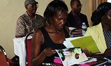 Photo: Goretti Kyebajia, a health facility staff from Namutumba district, reviews the MNP materials.