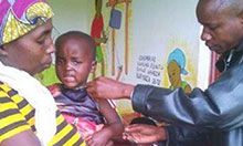 A health worker takes arm circumference and weight measurements on a 2-3 year old child being held by his mother. The child is making a distressed face.