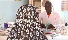 A woman speaks with a doctor at a health clinic