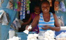 Photo of a woman selling food at a market stall