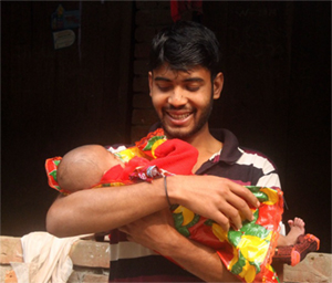 Photo of smiling Jewel holding his baby